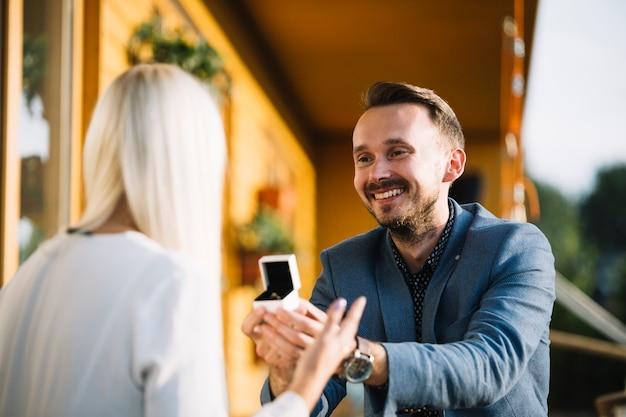 彼女のガールフレンドに婚約指輪を提供する男