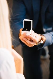 婚約指輪を含む赤いベルベットボックスと男性の手