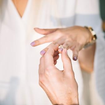 彼のガールフレンドの指に婚約指輪を入れて男の手のクローズアップ