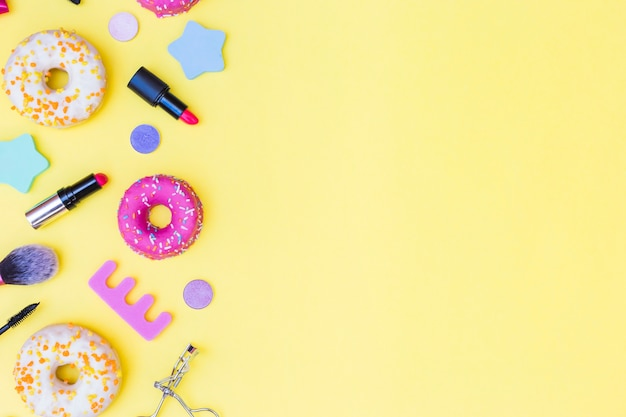 ドーナツのオーバーヘッドビュー。口紅;まつ毛カーラー;黄色の背景にメイクブラシとつま先の仕切り