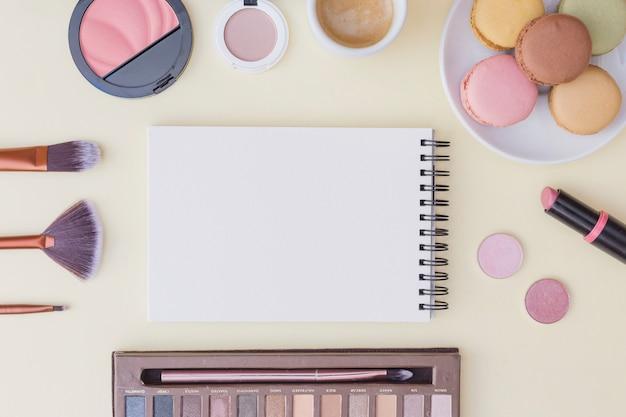 コーヒーとスパイラルのメモ帳のオーバーヘッドビュー;マカロンや化粧品