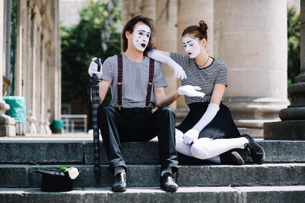 Несчастный мужчина и женщина-художник-мим, сидящий на лестнице
