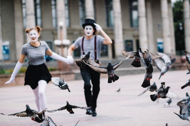 走っているママのカップルの近くに飛んでいる鳩