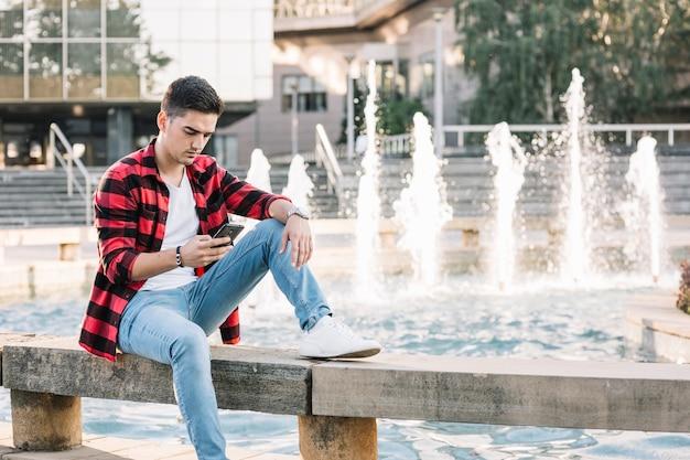 携帯電話を使って噴水の近くに座っている男