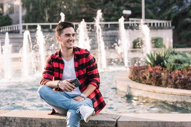 携帯電話を持っている噴水の前に座っている幸せな男