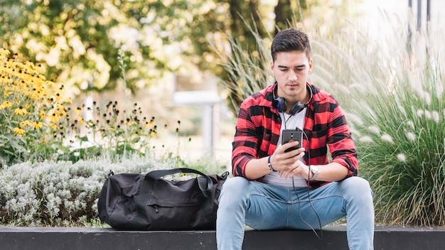 スマートフォンの画面を見ている若い男