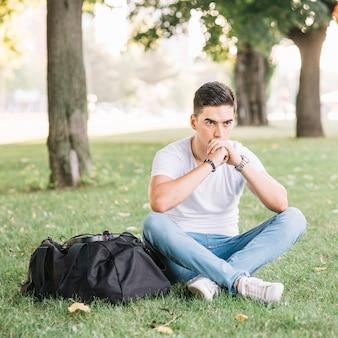 草の上に座っている熟視された若い男
