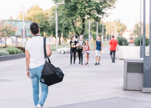 通りを歩いている男の背面図