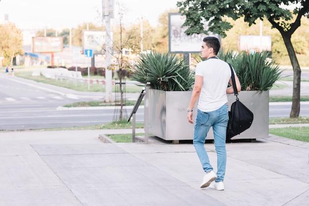 ストリートで歩くスタイリッシュな若い男