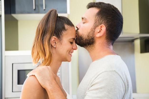 Мужчина целует жену на лбу