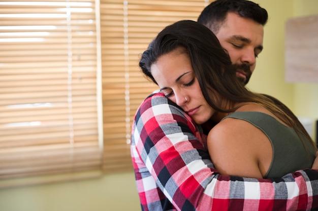 Мужчина обнимает жену дома
