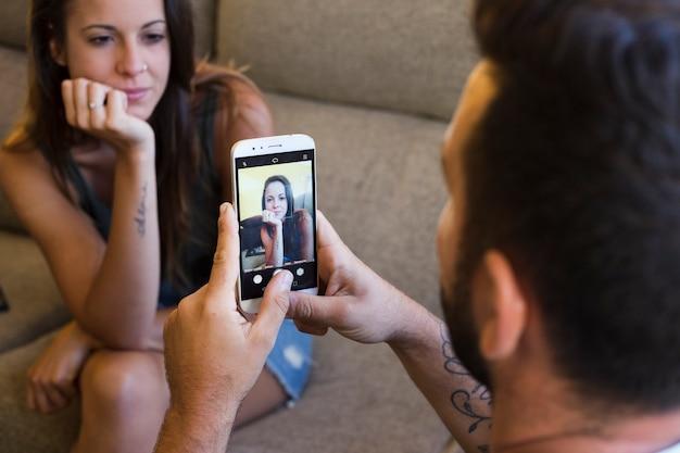 Человек, нажимая фотографию своей жены на смартфоне