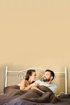 お互いを見てベッドに横たわっている幸せなカップル