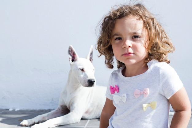 犬の前に立っている女の子の肖像
