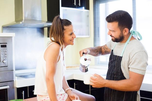 カップルでコーヒーを注ぐ彼女の夫を見て美しい女性