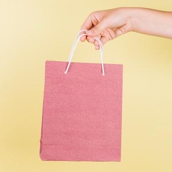黄色の背景にピンクの紙のショッピングバッグを保持している人の手