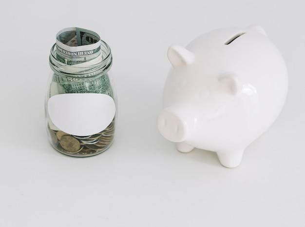 Белая копилка и открытая банка монет на белом фоне