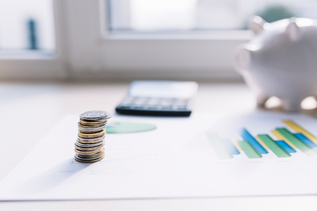 Монета стек на графике с калькулятором и копилка за столом