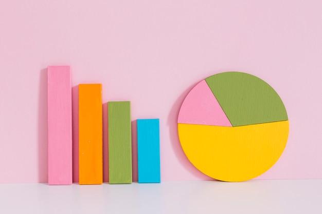 ピンクの背景上に机の上にカラフルな棒グラフと円グラフ