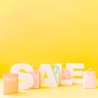 黄色の背景に手紙の販売の前に小さなピンクのショッピングバッグ
