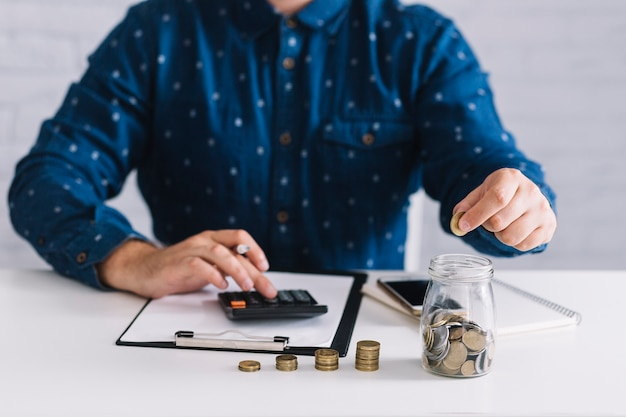 Крупный план человека расчета прибыли с помощью калькулятора на белом столе