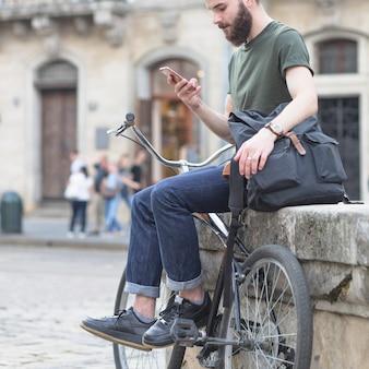 Человек сидит со своим велосипедом с помощью мобильного телефона