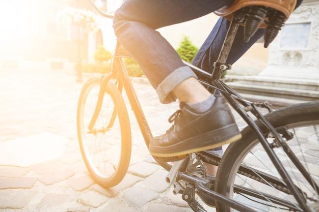 屋外で、自転車に乗っている人の足のクローズアップ