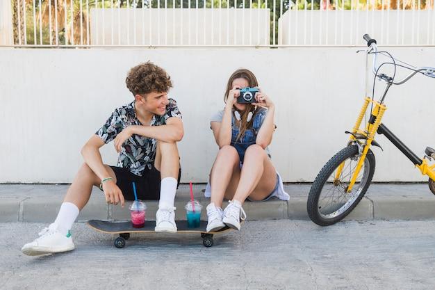カメラで写真を撮っている彼のガールフレンドを見ている男