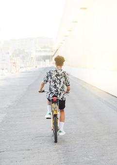 ストリートに乗っている若い男の自転車のリアビュー