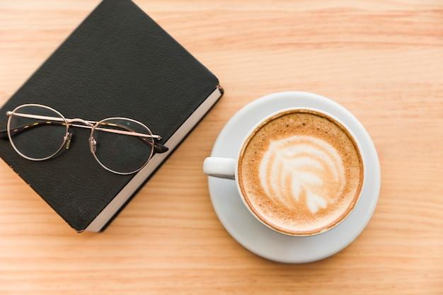 日記と木製の背景に眼鏡を持つコーヒーのカップ
