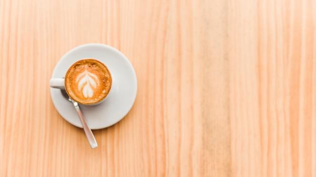 木製の背景にコーヒーラテのオーバーヘッドビュー