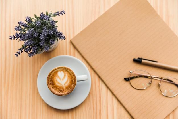 木製の机の上にコーヒーラテ、文房具、ラベンダーの花
