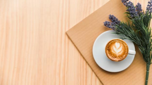木製の背景にコーヒーラテ、ノートブック、ラベンダーの花