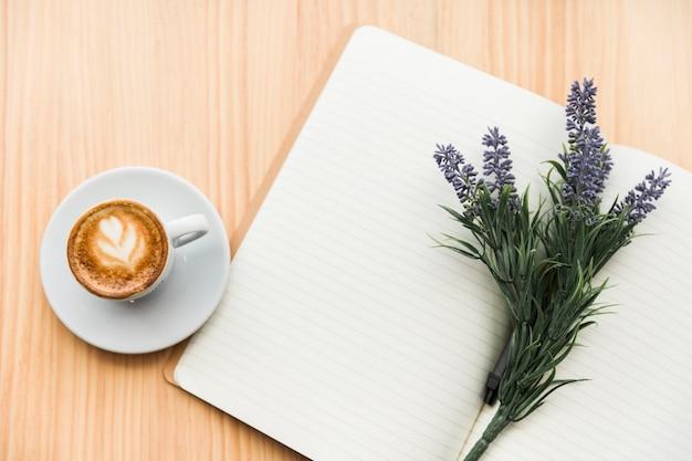 木製の机の上にコーヒーラテ、ラベンダーの花とノート