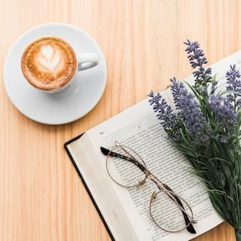 木製の机の上にコーヒーラテ、ラベンダーの花、眼鏡、ノート
