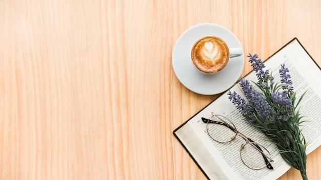 木製の背景にコーヒーラテ、ラベンダーの花、眼鏡、ノートブックのオーバーヘッドビュー