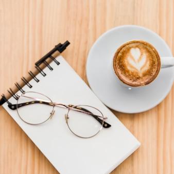 木製の机の上にスパイラルのメモ帳、眼鏡、コーヒーラテッ
