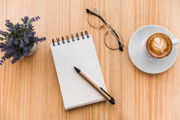 木製の背景にコーヒーラテ、スパイラルメモ帳、眼鏡、ラベンダーの花