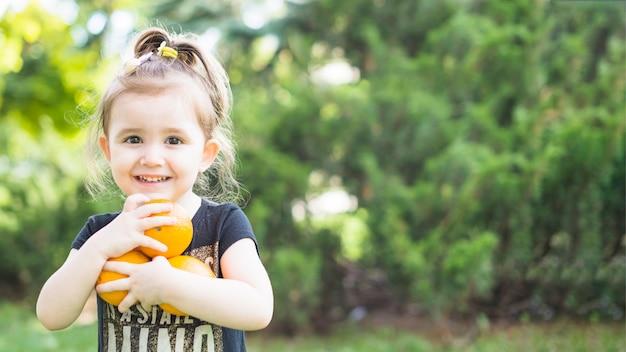 公園に新鮮なオレンジを持っている笑顔の女の子