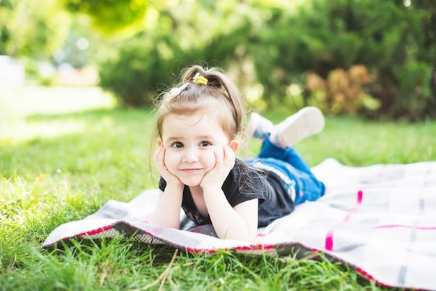 緑の草の上に毛布に横たわっている笑顔の美しい少女