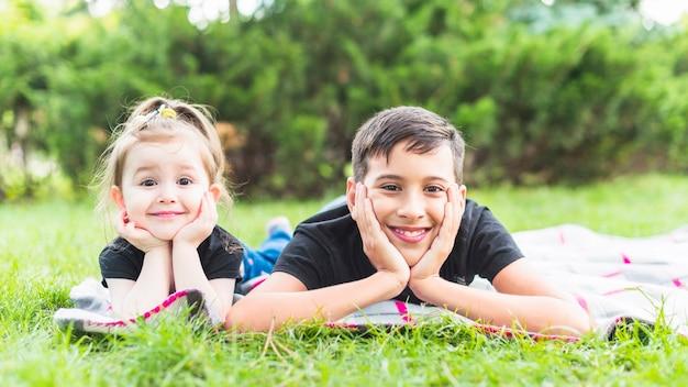 緑の草の上に毛布に横たわっている笑顔の兄弟姉妹