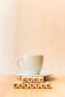 木製の表面にコーヒーのカップとおはよう立方体ブロックのクローズアップ