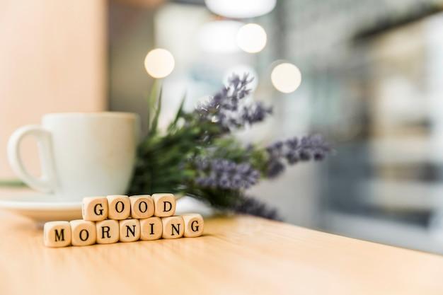 木製の机の上にコーヒーのカップとおはよう立方体ブロック