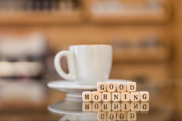 おはよう立方体ブロックと反射ガラスの机の上にコーヒーカップ