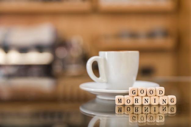ガラスのカウンターでコーヒーのカップとおはようの木製ブロック