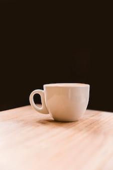 黒の背景の上に机の上に白いコーヒーカップ
