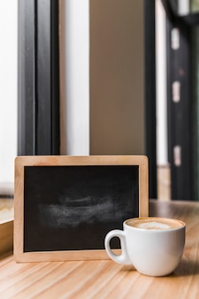 木製の机の上に黒いスレートを持つコーヒーラテ