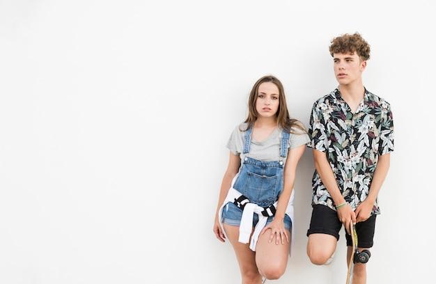 白い背景に彼女のガールフレンドの近くに立ってスケートボードを持つ男