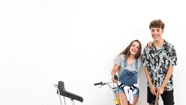 白い背景に自転車とスケートボードを持っているカップル
