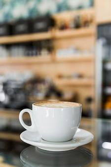 カフェの反射ガラスにアートラテットを入れたカプチーノコーヒー